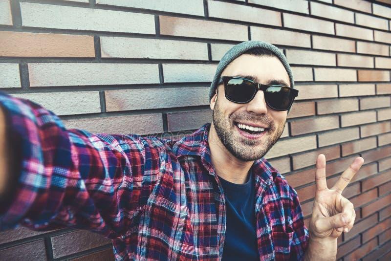 Το εύθυμο μοντέρνο άτομο στα γυαλιά ηλίου και το γκρίζο καπέλο παίρνει ένα selfie, που στέκεται ενάντια στον καφετή τουβλότοιχο στοκ εικόνα με δικαίωμα ελεύθερης χρήσης
