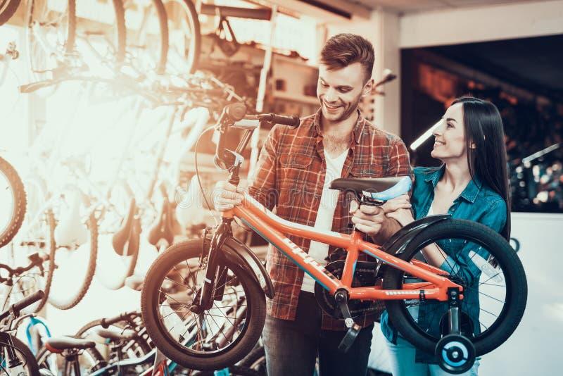 Το εύθυμο νέο ζεύγος επιλέγει το ποδήλατο παιδιών στο κατάστημα στοκ φωτογραφία με δικαίωμα ελεύθερης χρήσης