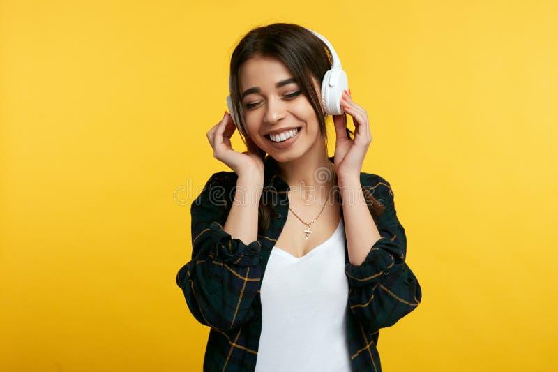 Το εύθυμο νέο κορίτσι απολαμβάνει τον ήχο της μουσικής, κρατά τα χέρια στα ακουστικά, κλείνει τα μάτια από την ευχαρίστηση, πέρα  στοκ φωτογραφίες