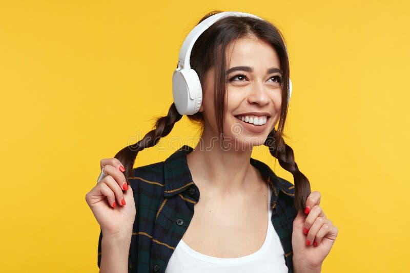 Το εύθυμο νέο κορίτσι με τα άσπρα ακουστικά, ακούει μουσική και αισθάνεται ευτυχές, παίζοντας με τις ουρές πόνι της, κοιτάζοντας  στοκ εικόνα