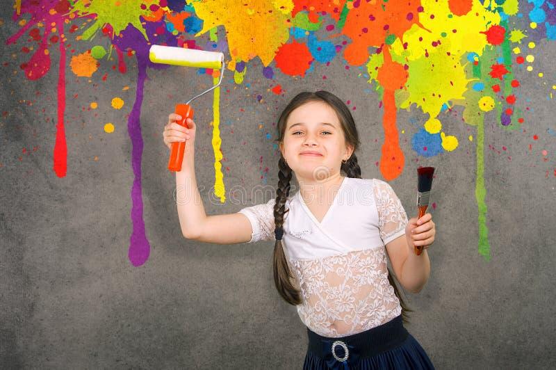 Το εύθυμο χαμογελώντας νέο μικρό κορίτσι που το παιδί επισύρει την προσοχή στον τοίχο υποβάθρου χρωμάτισε τα χρώματα κάνοντας τις στοκ φωτογραφία