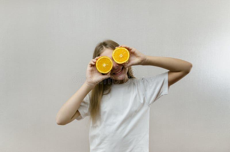 Το εύθυμο όμορφο κορίτσι κρατά στα μισά των πορτοκαλιών μισών Θετικές συγκινήσεις r Χορτοφάγος και Vegan στοκ φωτογραφία με δικαίωμα ελεύθερης χρήσης