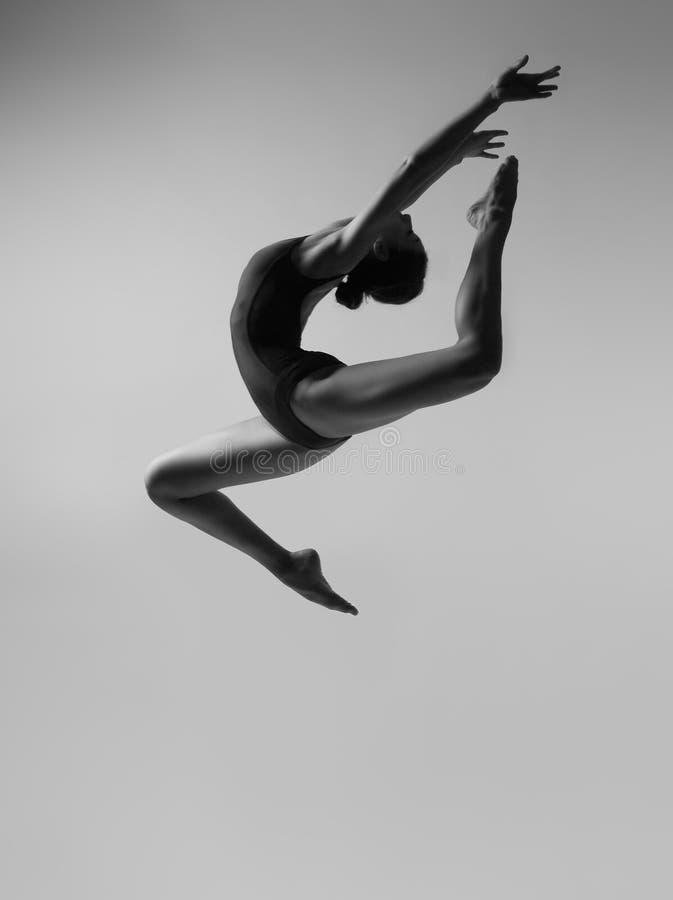 Το εύκαμπτο κορίτσι σε ένα μαύρο μαγιό κάνει ένα όμορφο άλμα στοκ εικόνες