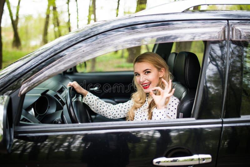 Το ελκυστικό κορίτσι κάθεται σε ένα σύγχρονο αυτοκίνητο Κοιτάζει μέσω του παραθύρου και παρουσιάζει εντάξει σημάδι στοκ εικόνα με δικαίωμα ελεύθερης χρήσης