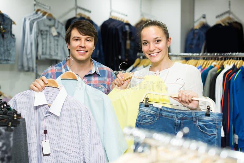 Το ζευγάρι επιλέγει τα ενδύματα στο κατάστημα στοκ εικόνες