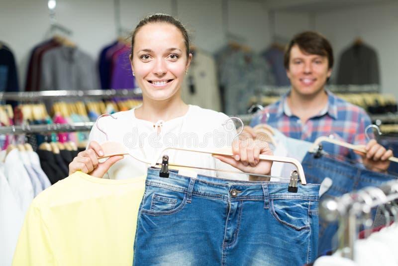 Το ζευγάρι επιλέγει τα ενδύματα στο κατάστημα στοκ φωτογραφία με δικαίωμα ελεύθερης χρήσης