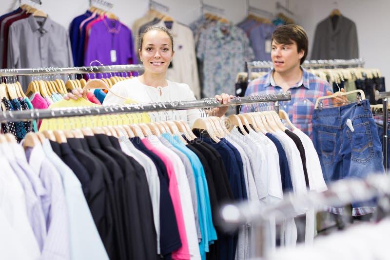 Το ζευγάρι επιλέγει τα ενδύματα στο κατάστημα στοκ φωτογραφία