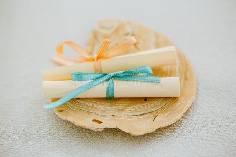 Το ζευγάρι των parchments ρόλων εγγράφου έδεσε με την κορδέλλα σε ένα θαλασσινό κοχύλι, μηνύματα αγάπης στοκ εικόνες