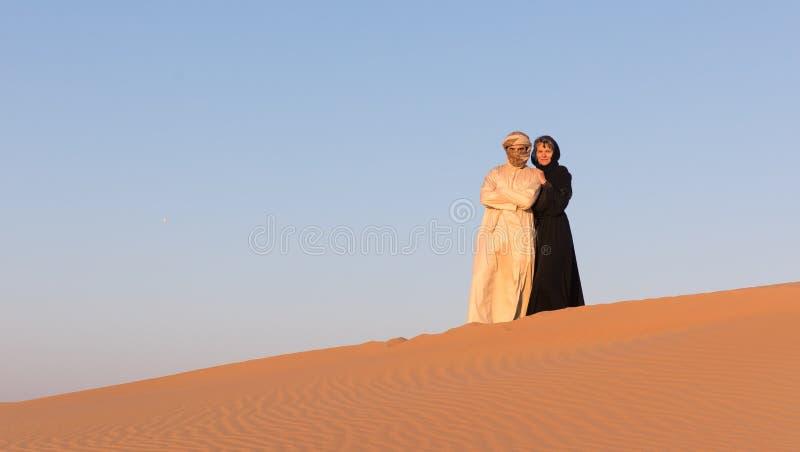 Το ζεύγος έντυσε στον παραδοσιακό αραβικό ιματισμό στην έρημο στοκ εικόνα