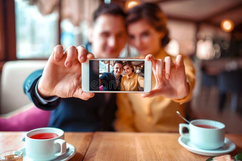 Το ζεύγος αγάπης κάνει selfie στη κάμερα στο εστιατόριο στοκ φωτογραφία