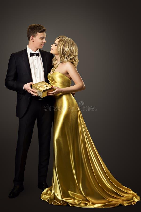 Το ζεύγος δίνει το παρόν κιβώτιο δώρων, πορτρέτο ομορφιάς γυναικών ανδρών μόδας στοκ φωτογραφία