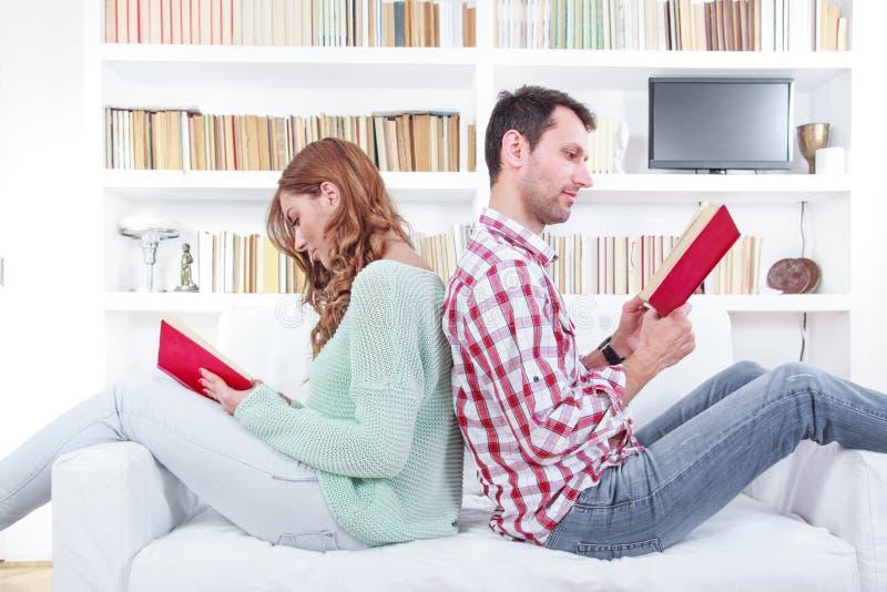 Το ζεύγος είναι καθισμένο μαζί σε έναν καναπέ πλάτη με πλάτη και είναι ρ στοκ εικόνες