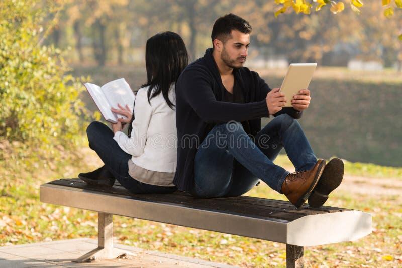 Το ζεύγος εξετάζει μια ταμπλέτα και ένα βιβλίο Digtial στοκ εικόνες