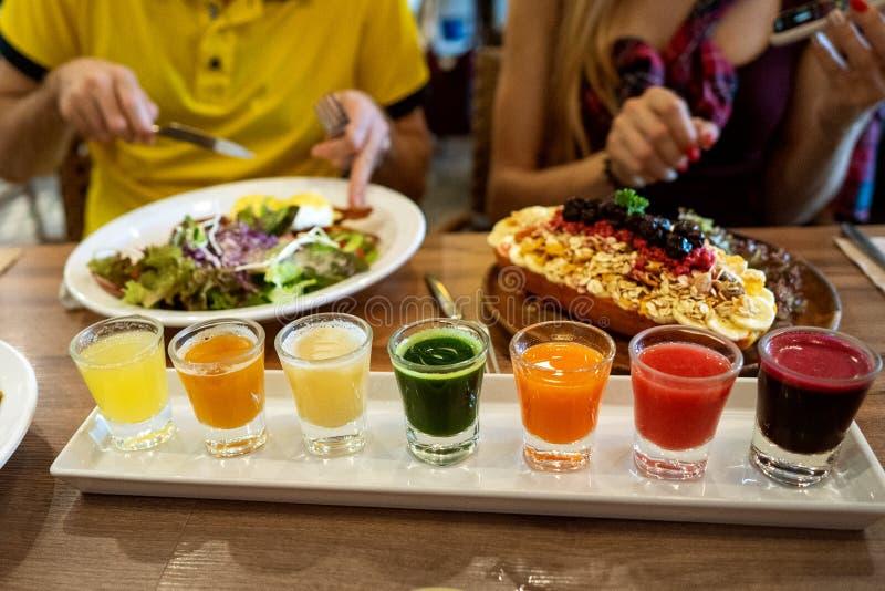 Το ζεύγος ερωτευμένο έχει το γεύμα σε ένα εστιατόριο με τα όμορφα πιάτα και ένα σύνολο φρέσκων χυμών στοκ φωτογραφίες