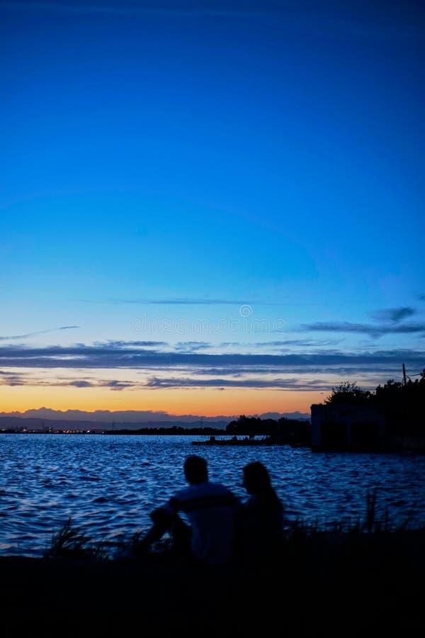 Το ζεύγος ερωτευμένο συλλογίζεται το ηλιοβασίλεμα στο Albufera της Βαλένθια στοκ φωτογραφίες