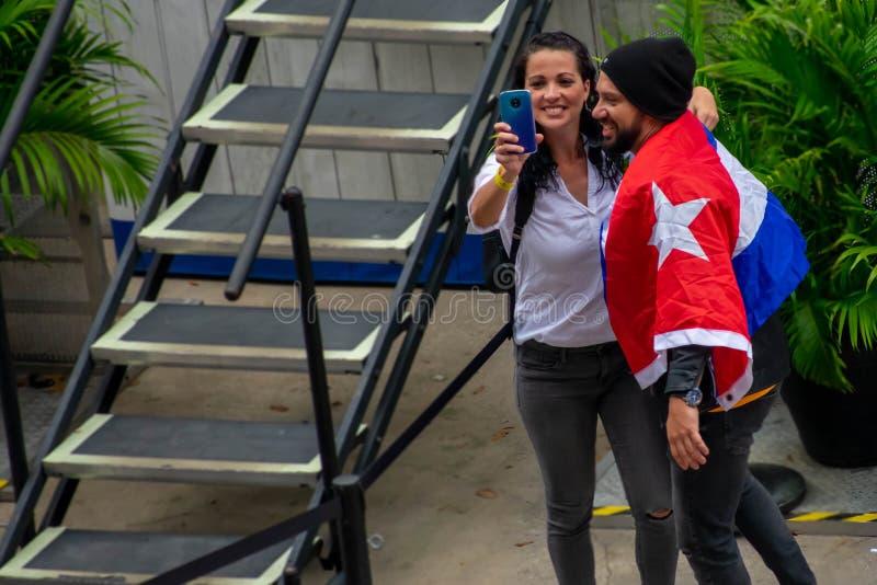 Το ζεύγος Κουβανών, που φορά μια σημαία, παίρνει ένα selfie στην έκθεση Gente de Zona σε Seaworld στη διεθνή περιοχή Drive στοκ εικόνες