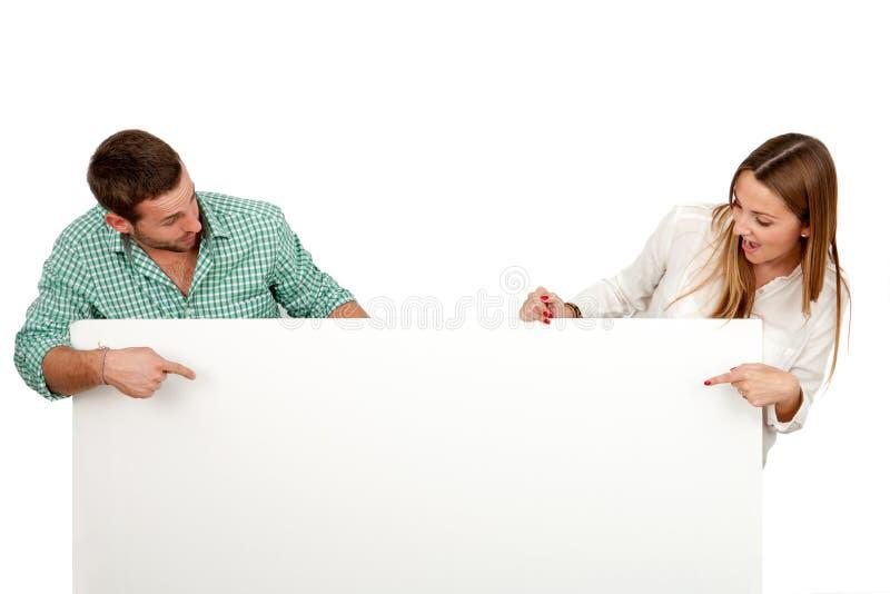 Το ζεύγος με έκπληκτος φαίνεται κενό χαρτόνι εκμετάλλευσης. στοκ εικόνες