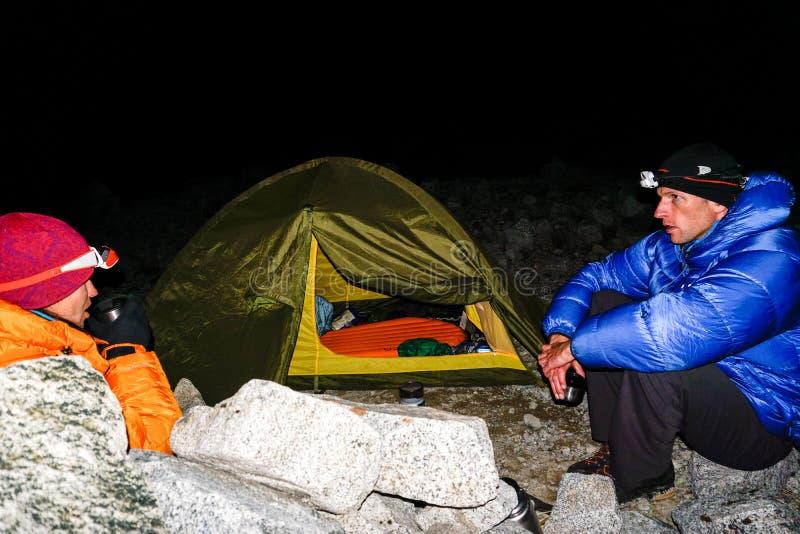 Το ζεύγος ορειβατών βουνών κάθεται έξω από μια σκηνή στο σκοτάδι και πίνει το τσάι υψηλό επάνω στο BLANCA οροσειρών στις Άνδεις τ στοκ φωτογραφίες