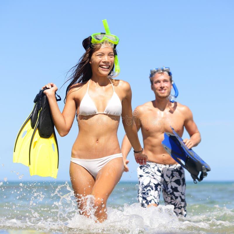 Το ζεύγος παραλιών που έχει τη διασκέδαση στο ταξίδι διακοπών κολυμπά με αναπνευτήρα στοκ εικόνα