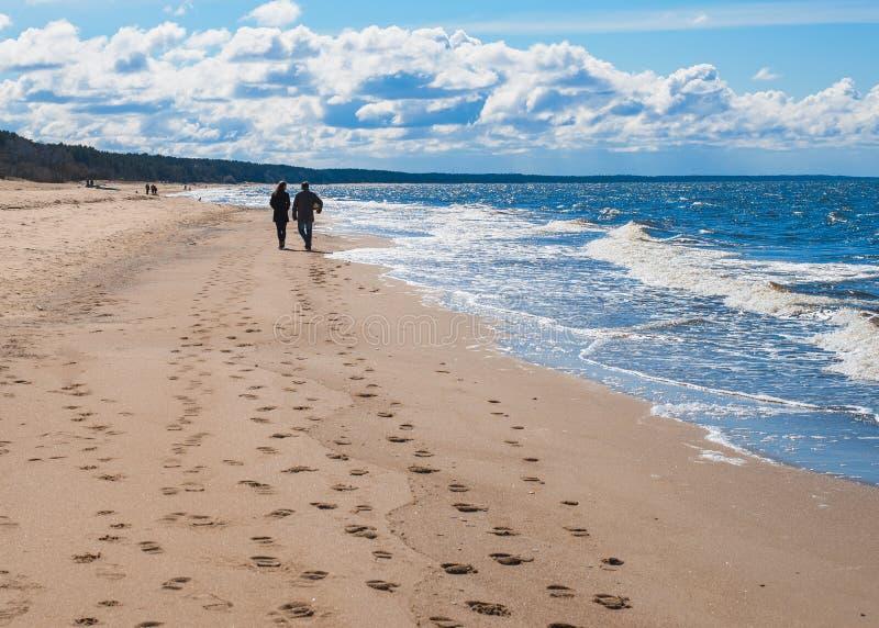 Το ζεύγος περπατά κατά μήκος της παραλίας κάτω από το μπλε ουρανό στοκ εικόνα με δικαίωμα ελεύθερης χρήσης