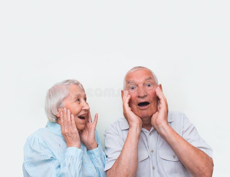 Το ζεύγος που εκπλήσσεται ηλικιωμένο με την αύξηση και των δύο χεριών στοκ φωτογραφίες