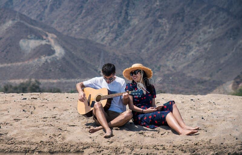 Το ζεύγος που τραγουδά και κιθάρα παιχνιδιού αγοράζει την παραλία στοκ φωτογραφία