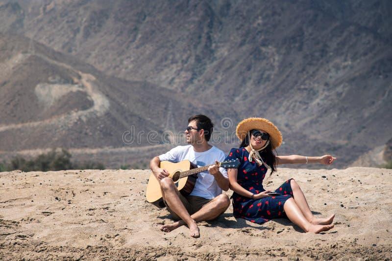 Το ζεύγος που τραγουδά και κιθάρα παιχνιδιού αγοράζει την παραλία στοκ εικόνες