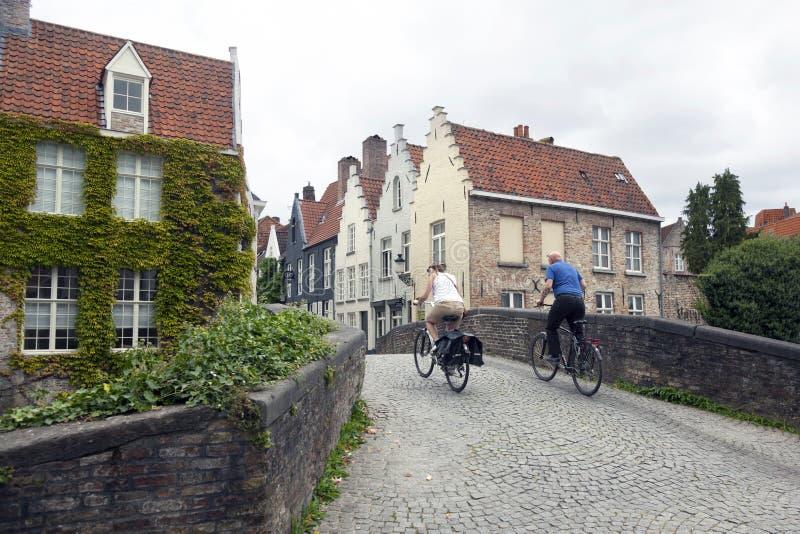 Το ζεύγος στα ποδήλατα προσπαθεί να οδηγήσει πέρα από την παλαιά μεσαιωνική γέφυρα στο cente στοκ φωτογραφίες