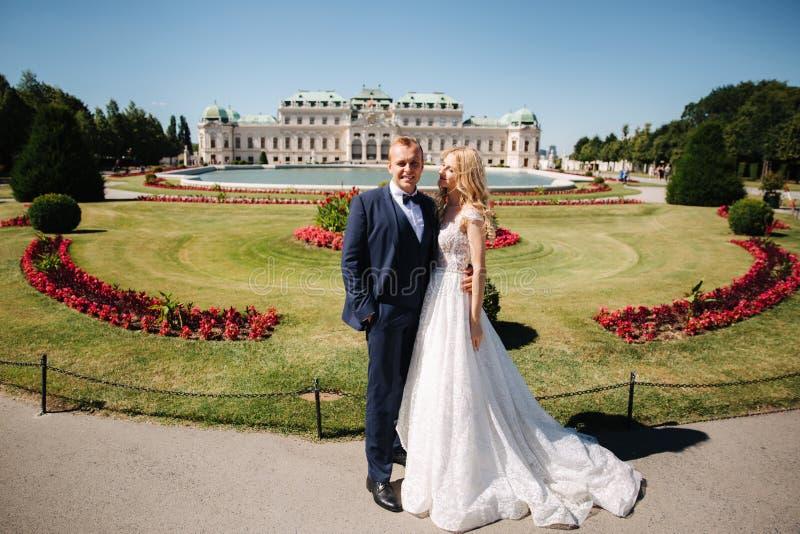 Το ζεύγος στη στάση γαμήλιων φορεμάτων κοντά στο παλάτι και έχει τη διασκέδαση στοκ φωτογραφία