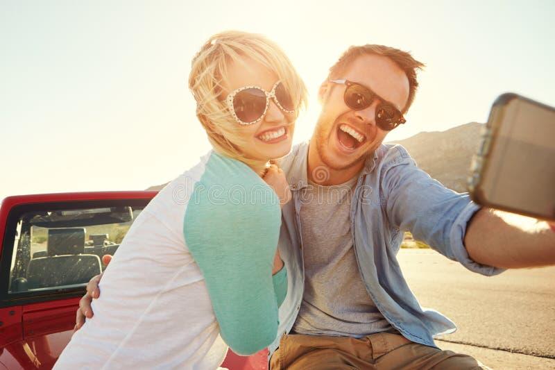 Το ζεύγος στο οδικό ταξίδι κάθεται στο μετατρέψιμο αυτοκίνητο που παίρνει Selfie στοκ φωτογραφίες με δικαίωμα ελεύθερης χρήσης