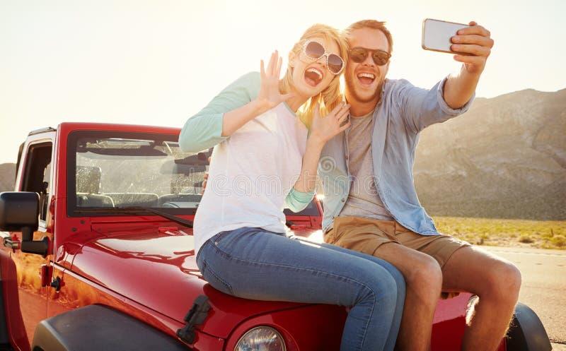 Το ζεύγος στο οδικό ταξίδι κάθεται στο μετατρέψιμο αυτοκίνητο που παίρνει Selfie στοκ φωτογραφία
