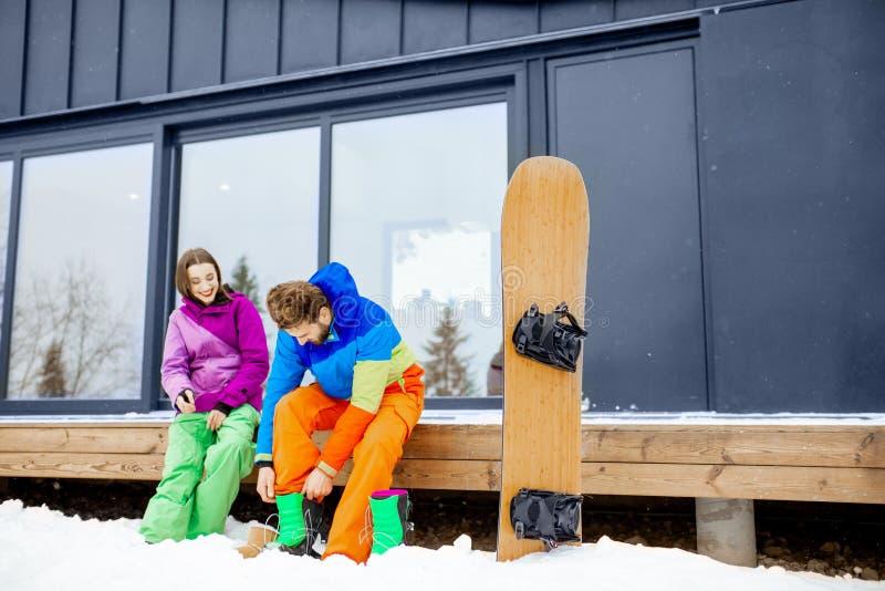 Το ζεύγος στο σκι ταιριάζει κοντά στο σύγχρονο σπίτι στα βουνά στοκ εικόνες