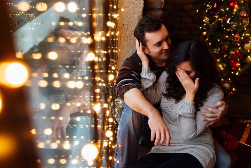 Το ζεύγος των εραστών αγκαλιάζει τη συνεδρίαση στο windowsill στο στούντιο σοφιτών Χριστουγέννων ο τύπος αγκαλιάζει το κορίτσι στοκ εικόνες με δικαίωμα ελεύθερης χρήσης