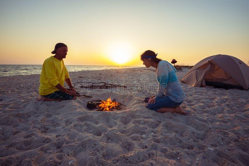 Το ζεύγος των ευτυχών τυχοδιωκτών κάθεται δίπλα στο κάψιμο της φωτιάς στο β στοκ φωτογραφία με δικαίωμα ελεύθερης χρήσης