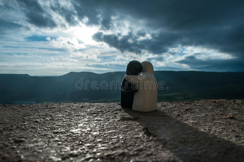 Το ζεύγος των κεραμικών αριθμών που αγκαλιάζει στο ηλιοβασίλεμα βουνών υποβάθρου, σκιαγραφεί δύο ρομαντικούς ανθρώπους που αγκαλι στοκ εικόνες