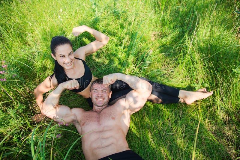Το ζεύγος των νέων αθλητικών τύπων βρίσκεται στην πράσινη χλόη μετά από το workout υπαίθρια στοκ φωτογραφία με δικαίωμα ελεύθερης χρήσης
