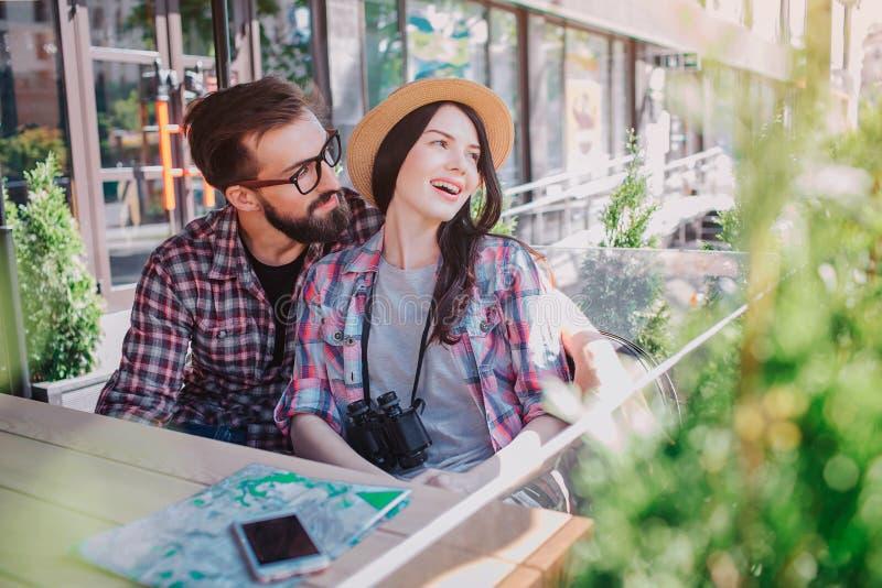 Το ζεύγος των νέων τουριστών είναι ερωτευμένο Κάθονται από κοινού Κοιτάζει στην πλευρά Το νέο γενειοφόρο άτομο την αγκαλιάζει και στοκ εικόνες