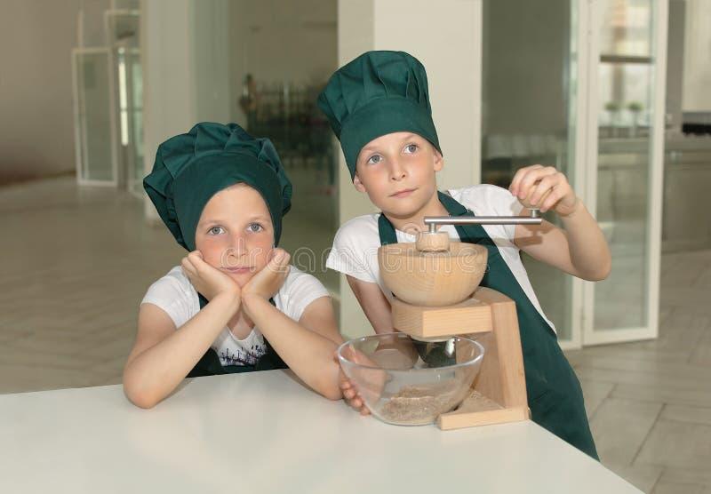 Το ζεύγος των νεολαιών μαγειρεύει τα κορίτσια αρχιμαγείρων στα πράσινα καλύμματα αρχιμαγείρων με το χειρωνακτικό μύλο κουζινών στοκ φωτογραφίες με δικαίωμα ελεύθερης χρήσης