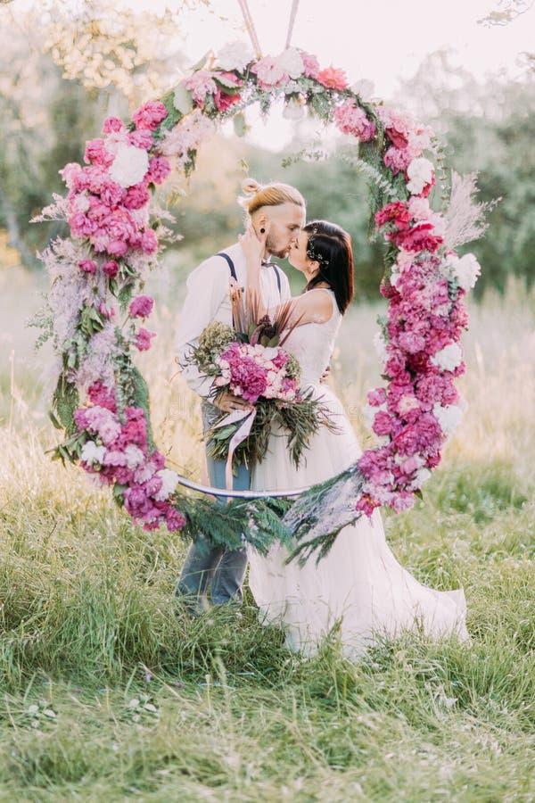 Το ζεύγος φιλά πίσω από τη γαμήλια peonies αψίδα στο ηλιόλουστο ξύλο Πορτρέτο κινηματογραφήσεων σε πρώτο πλάνο στοκ φωτογραφίες με δικαίωμα ελεύθερης χρήσης
