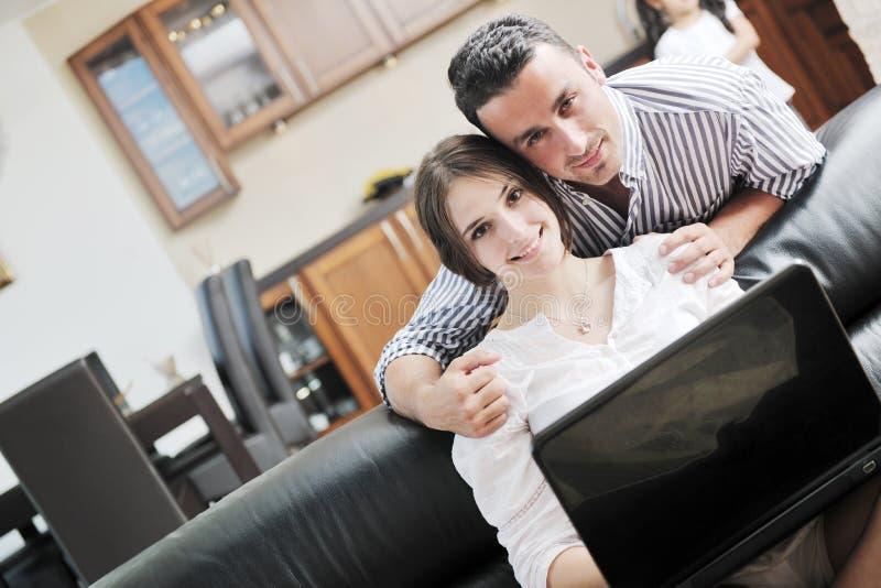Το ζεύγος χαλαρώνει και εργάζεται στο φορητό προσωπικό υπολογιστή στο σπίτι στοκ εικόνες με δικαίωμα ελεύθερης χρήσης