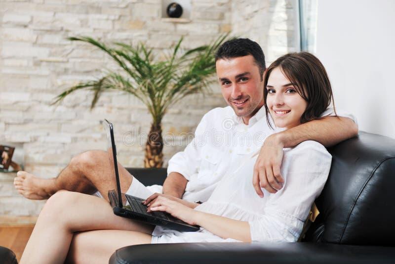 Το ζεύγος χαλαρώνει και εργάζεται στο φορητό προσωπικό υπολογιστή στο σπίτι στοκ φωτογραφία με δικαίωμα ελεύθερης χρήσης