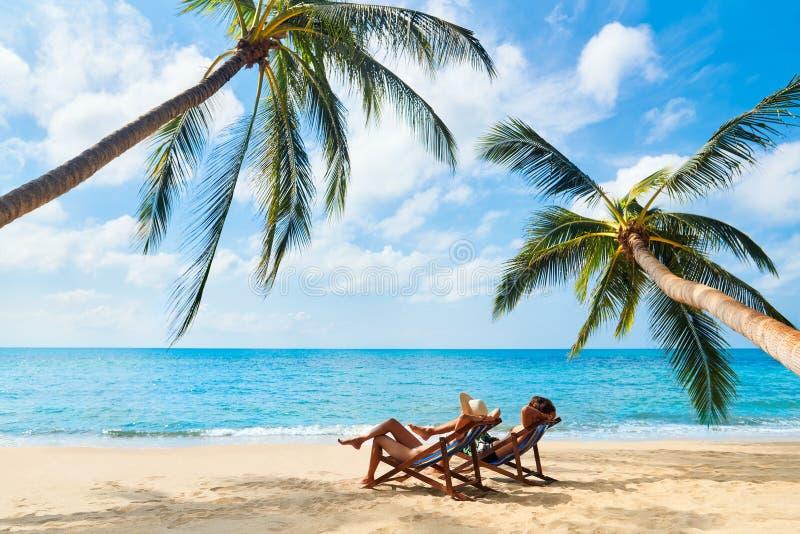 Το ζεύγος χαλαρώνει στην παραλία απολαμβάνοντας την όμορφη θάλασσα στο τροπικό νησί στοκ φωτογραφία