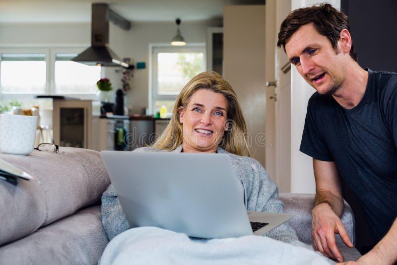 Το ζεύγος χαλαρώνει και εργάζεται στο φορητό προσωπικό υπολογιστή στο σύγχρονο καθιστικό στοκ εικόνες