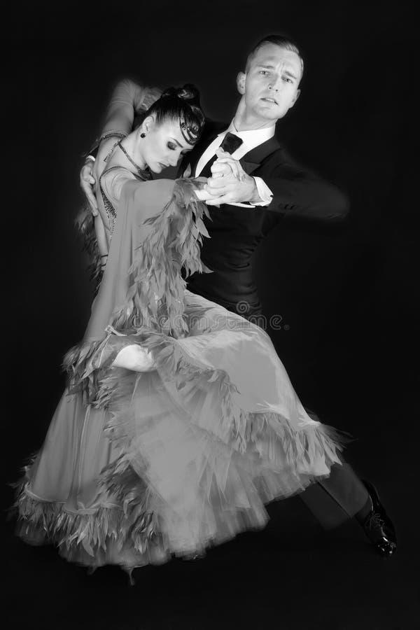 Το ζεύγος χορού Ballrom σε έναν χορό θέτει απομονωμένος στο μαύρο υπόβαθρο στοκ φωτογραφία