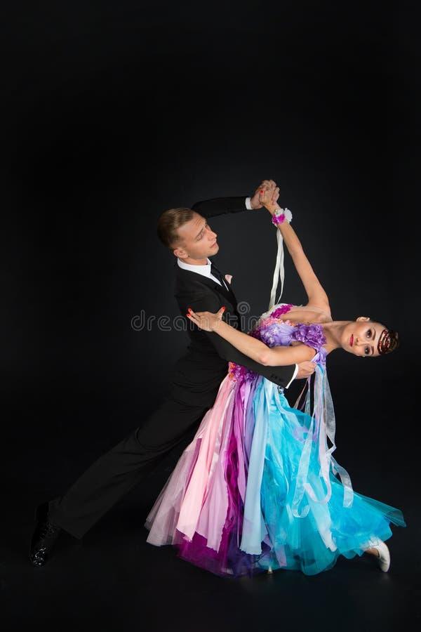 Το ζεύγος χορού Ballrom σε έναν χορό θέτει απομονωμένος στο μαύρο υπόβαθρο στοκ φωτογραφίες