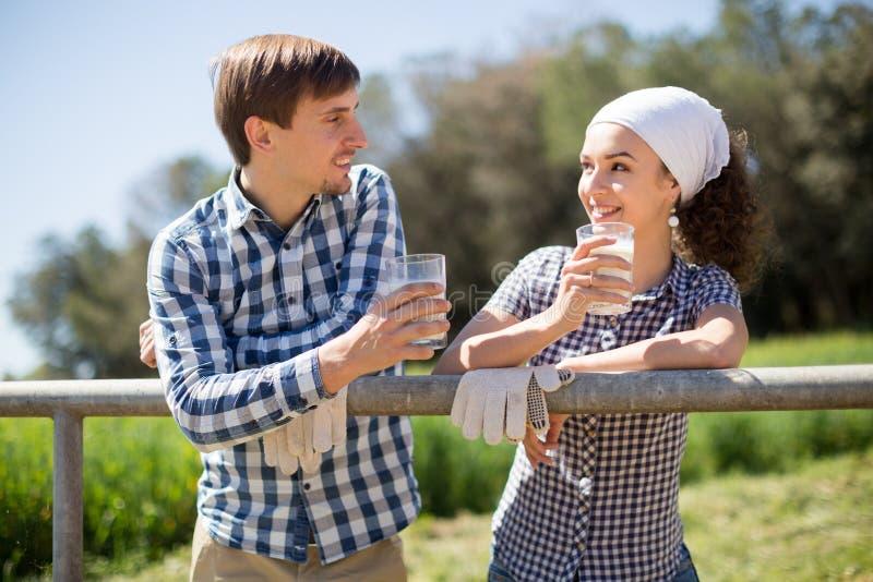 Το ζεύγος χώρας των αγροτών πίνει το γάλα στον τομέα fenc πλησίον στοκ φωτογραφίες