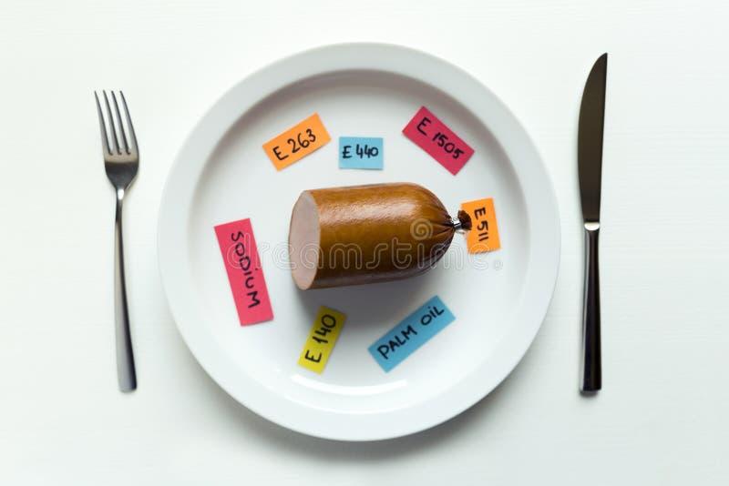 Το ζωηρόχρωμο έγγραφο σημειώνει τις πρόσθετες ουσίες τροφίμων ονομασίας και το λουκάνικο στο πιάτο με το δίκρανο και το μαχαίρι,  στοκ φωτογραφία με δικαίωμα ελεύθερης χρήσης