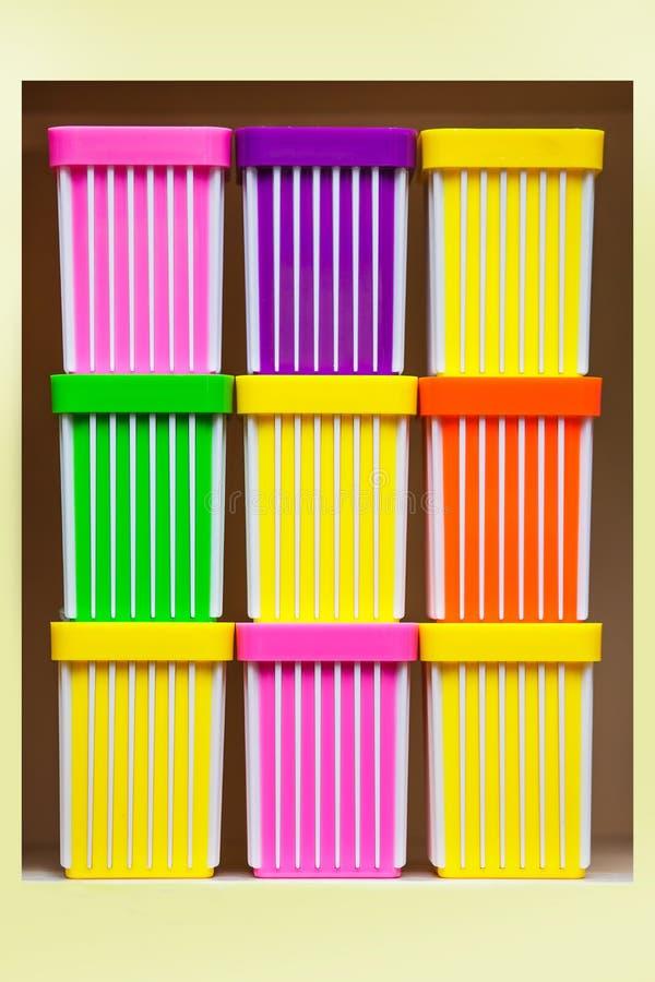 Το ζωηρόχρωμο πλαστικό φλυτζάνι απομόνωσε το ρόδινο κιτρινοπράσινο πορτοκαλί πολύχρωμο ράφι χαρτικών παλετών στοκ εικόνα