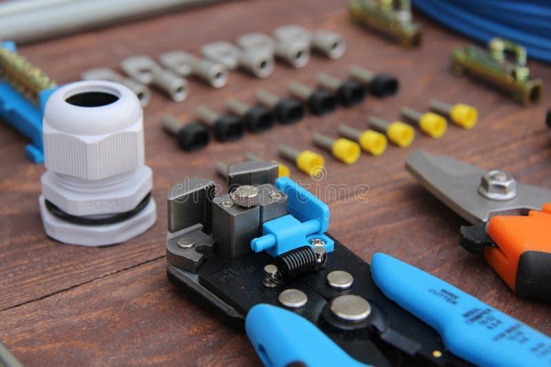 Το ηλεκτρικό stripper καλωδίων εργαλείο στο πρώτο πλάνο βρίσκεται σε μια ξύλινη επιφάνεια στοκ φωτογραφία