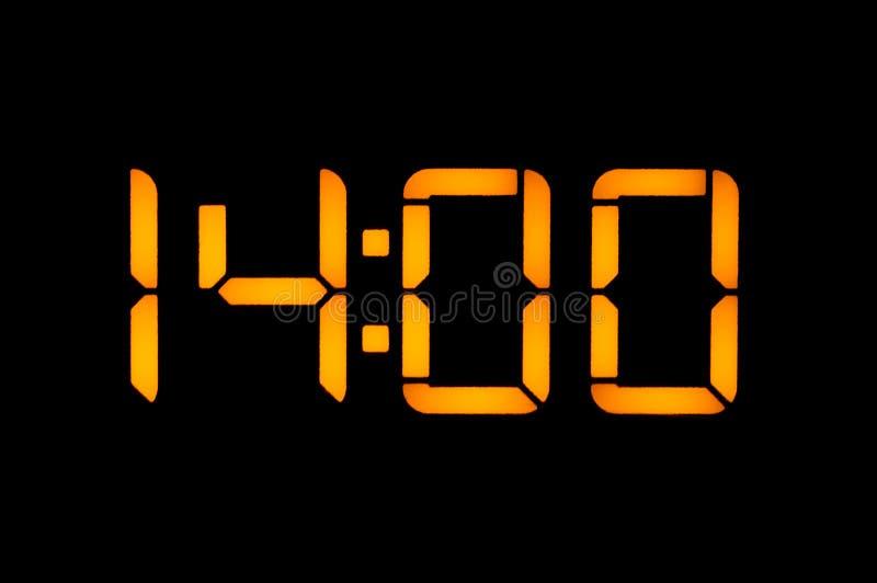 Το ηλεκτρονικό ψηφιακό ρολόι με τους κίτρινους αριθμούς σε ένα μαύρο υπόβαθρο παρουσιάζει στο χρόνο δεκατέσσερις μηές μηές η ώρα  στοκ φωτογραφίες